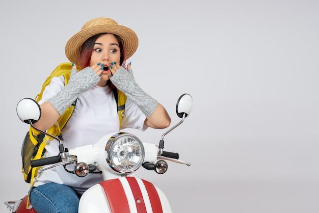 Vorderansicht junger weiblicher tourist, der auf motorrad auf weißem wandgeschwindigkeitsfahrzeugfoto-fahrttouristen sitzt