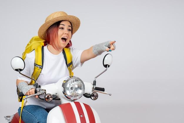 Vorderansicht junger weiblicher tourist, der auf motorrad auf weißer wandfahrzeugfrau-geschwindigkeitsfahrtourist sitzt