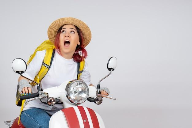 Vorderansicht junger weiblicher tourist, der auf motorrad auf weißer wandfahrzeugfrau-geschwindigkeitsfoto-fahrt-touristen sitzt
