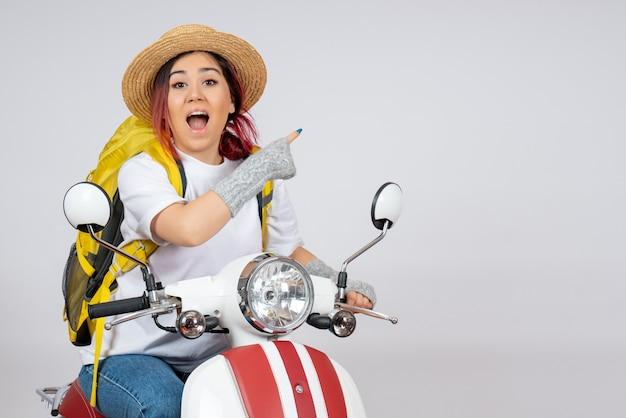 Vorderansicht junger weiblicher tourist, der auf motorrad auf weißer wandfahrzeugfrau-geschwindigkeitsfoto-fahrttourist sitzt