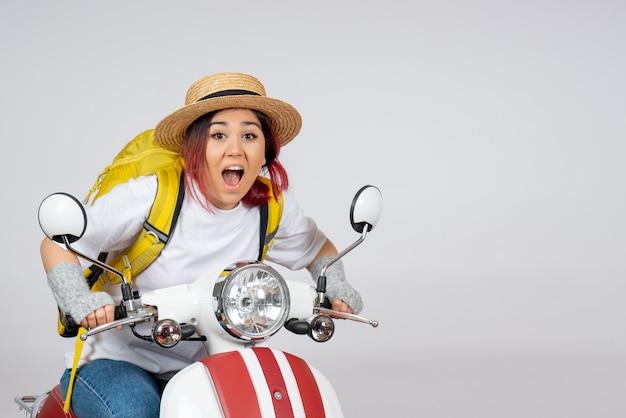 Vorderansicht junger weiblicher tourist, der auf motorrad auf weißer wandfrau tourist fährt fahrzeuggeschwindigkeitsfotos sitzt