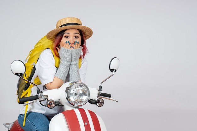 Vorderansicht junger weiblicher tourist, der auf motorrad auf weißer wandgeschwindigkeitsfrau-touristenfahrzeugfahrt sitzt