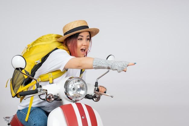 Vorderansicht junger weiblicher tourist, der auf motorrad auf weißer wandgeschwindigkeitsfrauenfahrzeugfotofahrt sitzt