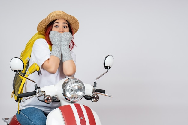 Vorderansicht junger weiblicher tourist, der auf motorrad sitzt, erschreckte auf fotofahrt des touristenfahrzeugs der weißen wandgeschwindigkeitsfrau