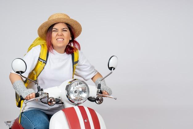 Vorderansicht junger weiblicher tourist, der motorrad auf weißem wandfrauen-touristenfahrzeuggeschwindigkeitsfoto reitet