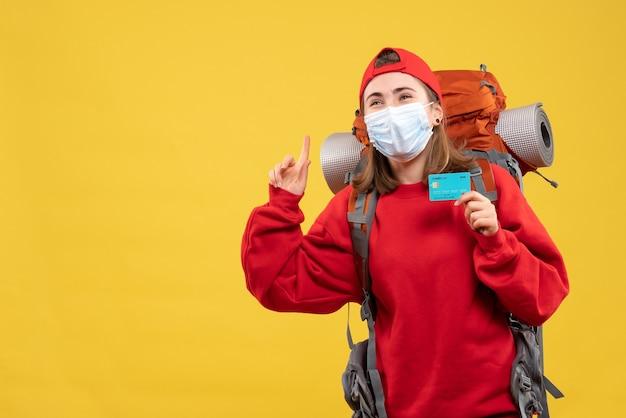 Vorderansicht junger weiblicher wanderer mit rucksack und maske, die kreditkarte hält, die an decke zeigt