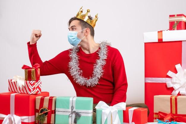 Vorderansicht junger weihnachtsmann mit maske, die auf bodenweihnachtsgeschenken sitzt
