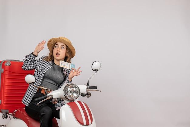 Vorderansicht junges mädchen auf moped, das ticket hochhält