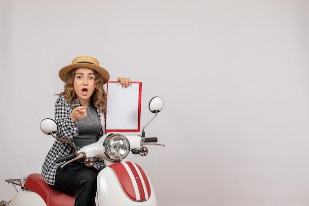 Vorderansicht junges mädchen auf moped hält zwischenablage nach vorne zeigend