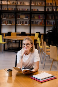 Vorderansicht junges mädchen, das an der bibliothek denkt
