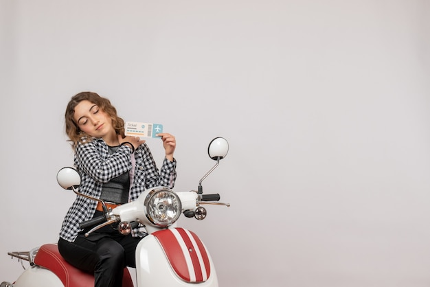 Vorderansicht junges mädchen mit geschlossenen augen auf moped-holding-ticket
