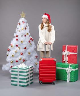 Vorderansicht junges mädchen mit rotem koffer, der nahe weißem weihnachtsbaum und geschenken steht