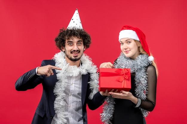 Vorderansicht junges paar mit geschenk feiern auf der roten wand party weihnachtsliebe