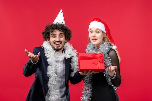 Vorderansicht junges paar mit geschenk feiern auf rotem boden party weihnachtsliebe