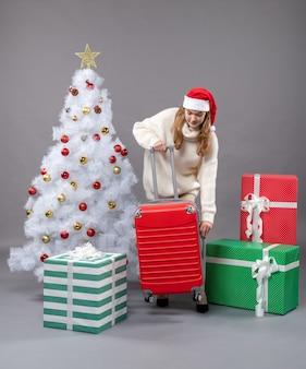 Vorderansicht junges weihnachtsmädchen, das roten koffer öffnet