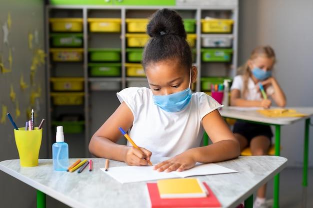 Vorderansicht kind, das in ihrem notizbuch schreibt