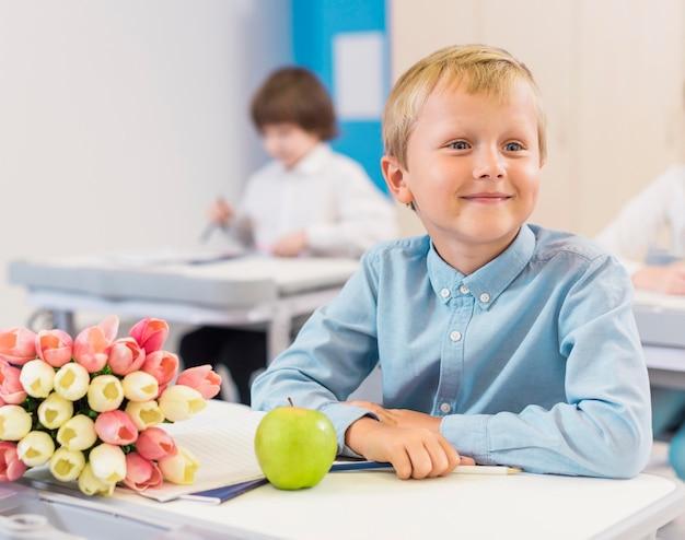 Vorderansicht kind sitzt neben geschenken für seinen lehrer
