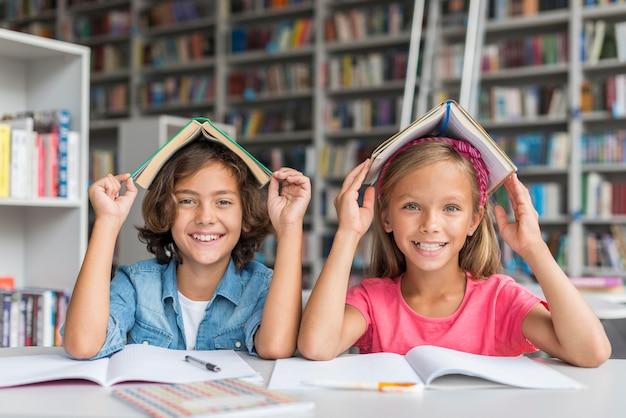 Vorderansicht kinder, die auf eine dumme weise an der bibliothek aufwerfen