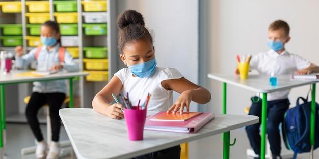 Vorderansicht kinder, die sich mit gesichtsmasken schützen