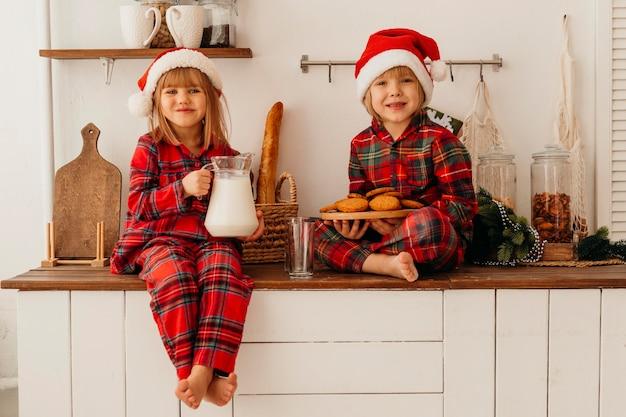 Vorderansicht kinder, die weihnachtsplätzchen essen
