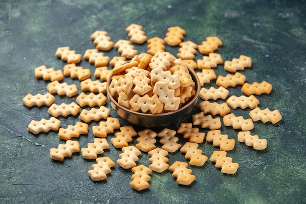 Vorderansicht kleine cracker in der platte auf dunkelgrauem hintergrund knusprige farbe snack cips salzbrot trockener zwieback essen pfeffer