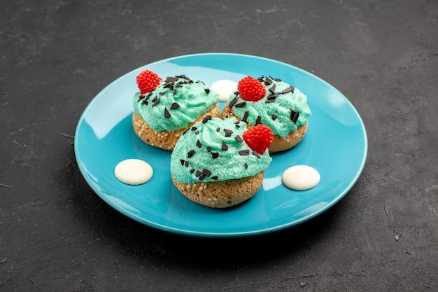 Vorderansicht kleine cremige kuchen köstliche süßigkeiten für tee im teller auf dunklem hintergrund sahnekuchen keks dessert teefarbe