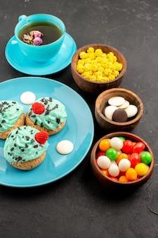 Vorderansicht kleine cremige kuchen mit tasse tee und süßigkeiten auf dunklem schreibtisch teecremekuchen keks dessertfarbe dessert