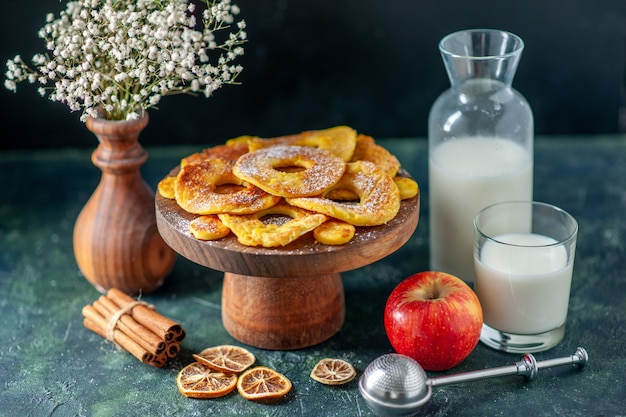 Vorderansicht kleine köstliche kuchen in ananasringform mit milch auf dunklem hotcake backen obstkuchen gebäckfarbe keks kekskuchen