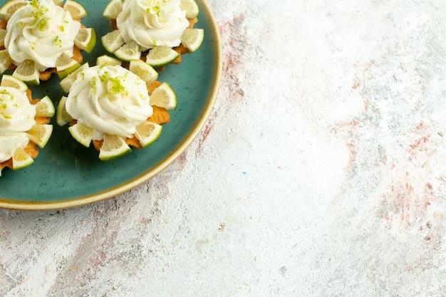 Vorderansicht kleine köstliche kuchen mit zitronenscheiben auf hellweißer oberfläche kuchenkeksplätzchen süßer teezucker