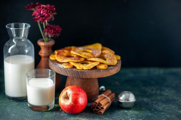 Vorderansicht kleine leckere kuchen in ananasringform mit milch auf der dunklen oberfläche