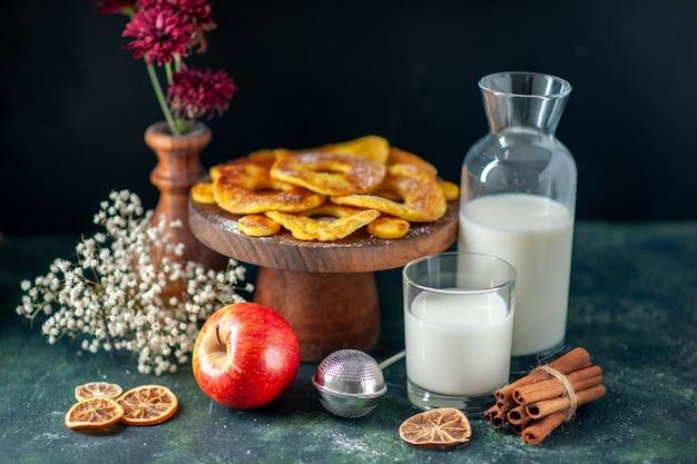 Vorderansicht kleine leckere kuchen in ananasringform mit milch auf dunklem hotcake backen kuchenfarbe kekskuchen obstkeks gebäck