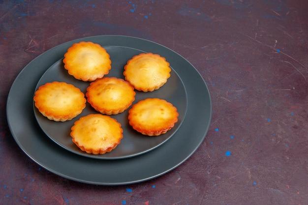 Vorderansicht kleine leckere kuchen in der platte auf dem dunklen hintergrund kuchen keks kuchen süßer tee keks zucker