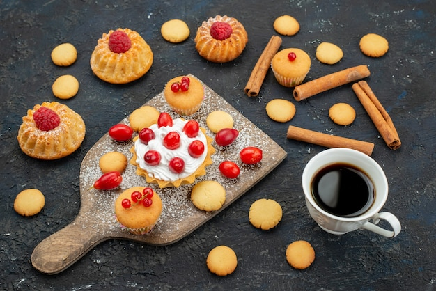 Vorderansicht kleine leckere kuchen mit sahne-zimt-kaffee und frischen früchten auf der dunklen oberfläche süße kekse kuchen dessert obst beere