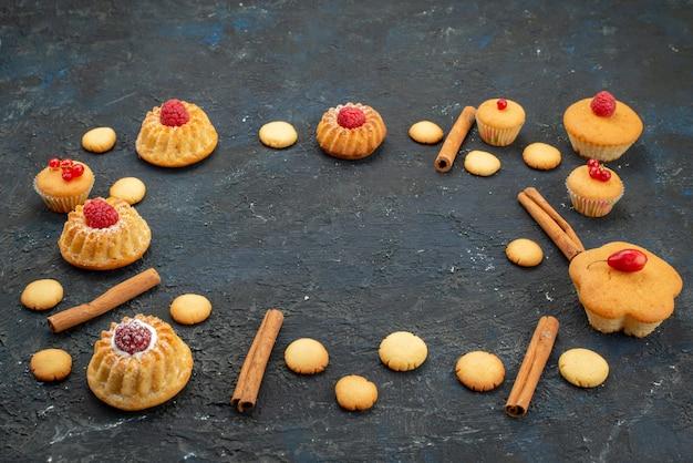 Vorderansicht kleine leckere kuchen mit sahnekeksen zimt auf dem dunklen schreibtisch keks kuchen dessert obst beere