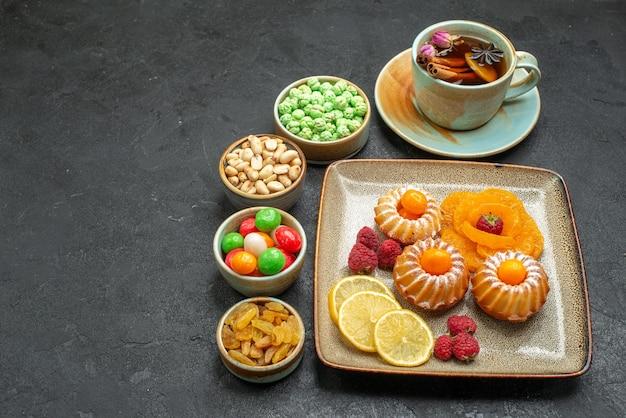 Vorderansicht kleine leckere kuchen mit süßigkeiten, früchten und nüssen auf grauraum