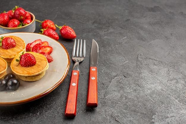 Vorderansicht kleine leckere pfannkuchen mit früchten auf der dunklen oberfläche kuchenfruchtkuchen