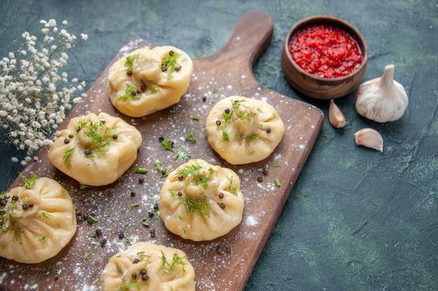 Vorderansicht kleine rohe knödel mit tomatensauce auf dunkelblauem tischfleisch teig teigküche gericht kuchen abendessen mahlzeit kochen