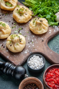 Vorderansicht kleine rohe knödel mit tomatensauce und gemüse auf dunkelblauer oberfläche kochen abendessen teig gericht mahlzeit küche fleisch