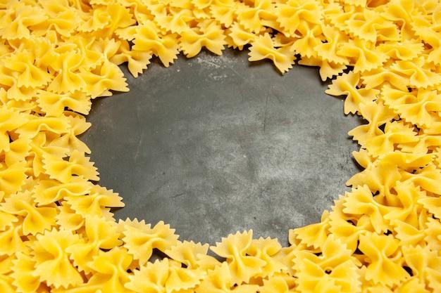 Vorderansicht kleine rohe nudeln auf dunklem foto viele teigwaren italienische pastafarbe