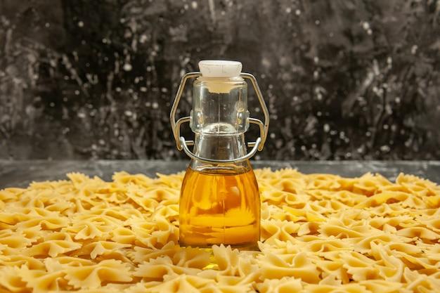 Vorderansicht kleine rohe nudeln mit öl auf dunklen vielen teignahrungsmahlzeiten farbfoto italienische pasta