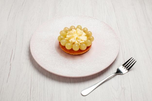 Vorderansicht kleine sahnetorte mit frischen trauben auf weißem hintergrund kuchen obstkuchen dessert keks keks