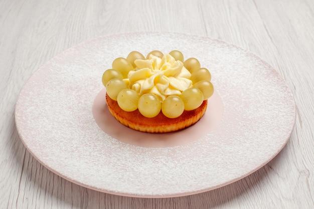 Vorderansicht kleine sahnetorte mit trauben auf weißem hintergrund torte obstkuchen dessert keks keks