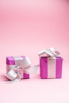 Vorderansicht kleine weihnachtsgeschenke auf rosa weihnachtsfarbgeschenkfoto neujahrsfeiertag