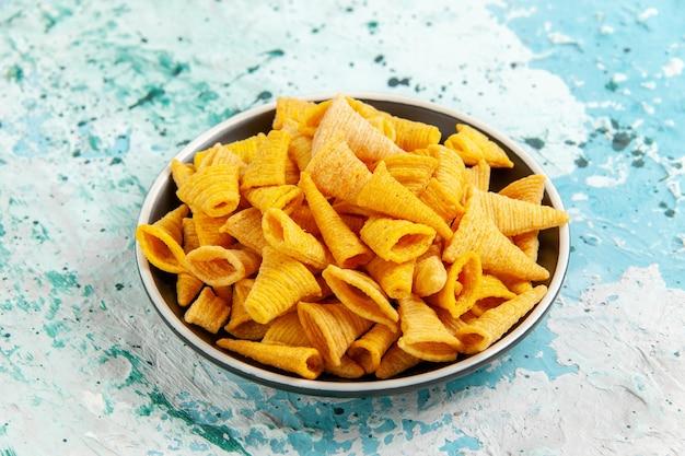 Vorderansicht kleine würzige chips innerhalb platte auf hellblauem schreibtisch