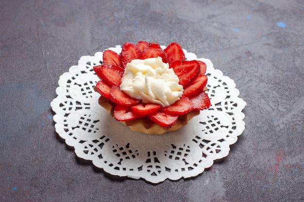 Vorderansicht kleiner cremiger kuchen mit geschnittenen früchten auf dunkler oberfläche
