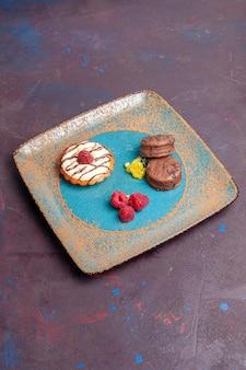 Vorderansicht kleiner cremiger kuchen mit schokoladenkeksen auf dunklem hintergrund biskuitzuckerkuchen süßer kuchen