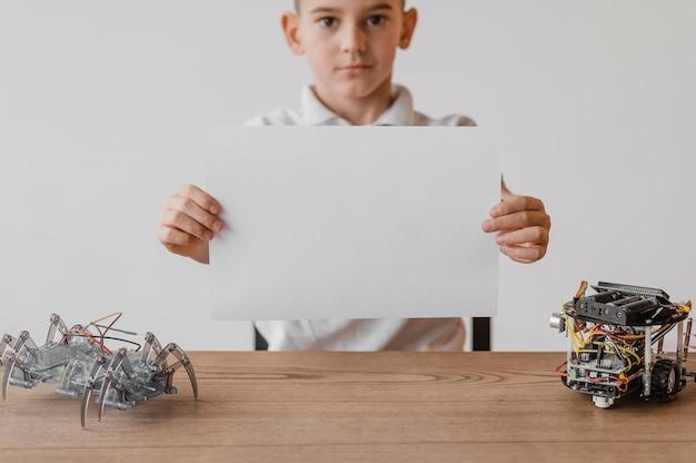 Vorderansicht kleiner junge, der ein leeres papier hält