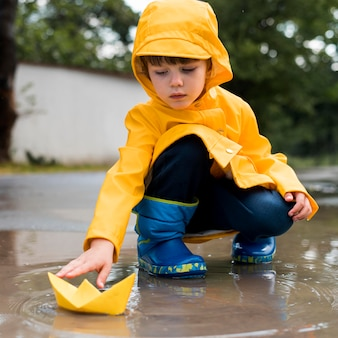 Vorderansicht kleiner junge, der mit einem papierboot spielt