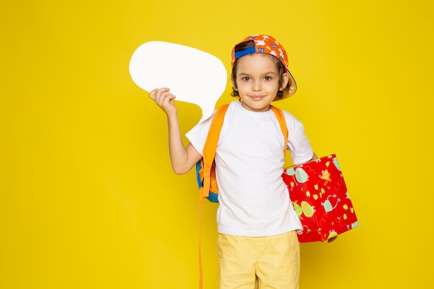 Vorderansicht kleiner junge im weißen t-shirt, das geschenk auf dem gelben boden hält