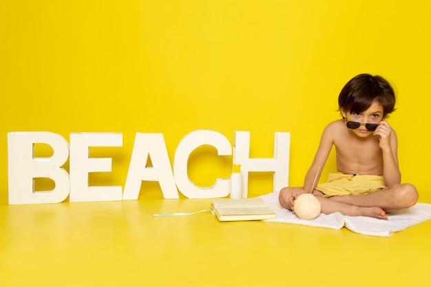 Vorderansicht kleiner junge in sonnenbrille auf gelbem boden